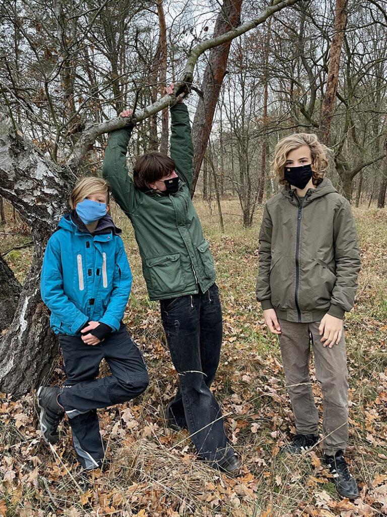 Drei Personen mit Schutzmasken im Wald